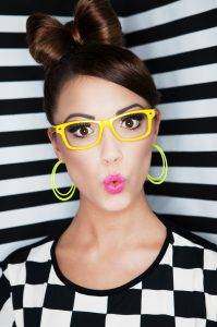 Attractive young surprised woman wearing glasses on stripy background